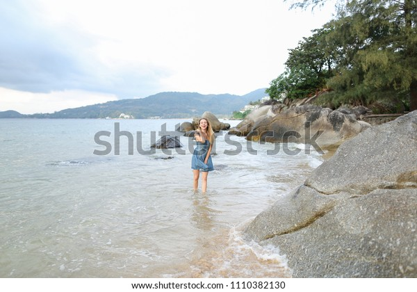 Young pretty girl wearing jeans sundress and walking barefoot on sand, morning sea shore. Concept of tropical summer vacations and resting.