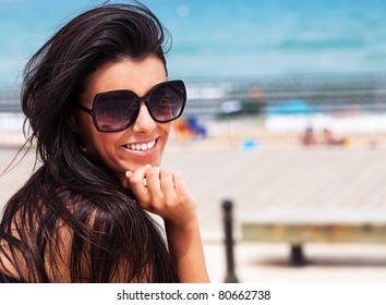 young pretty girl wearing sunglasses smiling with the beach as a background