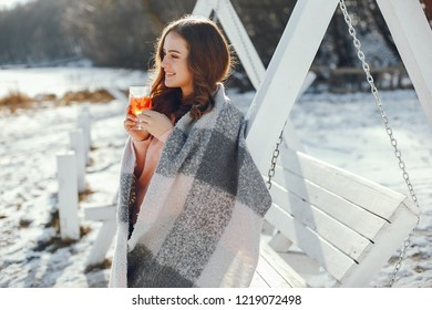 young pretty girl in winter park drinking mulledwine