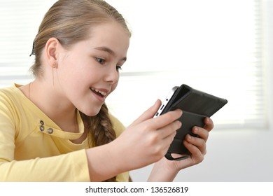 young pretty girl in a yellow jacket using tablet at home
