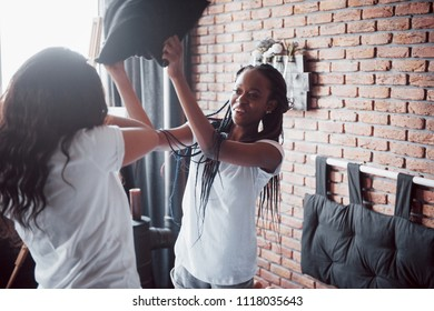 young pretty girls jumping on bed and fight pillows having fun at home.