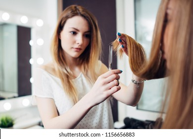 Young pretty hairdresser wearing casual clothes holding strand of long hair between fingers trimming the ends in beauty studio