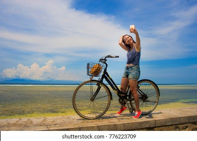 young pretty and happy Asian Chinese girl riding vintage bicycle on the beach taking selfie portrait picture with mobile phone to upload to internet social media in holiday and vacation concept