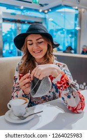 Young pretty and happy woman smiling and crocheting with gray cotton yarn in a coffee shop, handmade crochet project