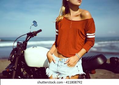 young pretty hipster girl Biker girl sitting  on vintage custom motorcycle Biker girl sitting Outdoor lifestyle portrait. jeans short denim, fashion style