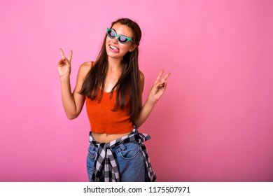 Young pretty hipster woman having fun showing tongue and posing on camera, casual hipster clothes vintage sunglasses, studio pink background.