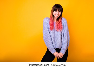 Young pretty hipster woman posing at yellow background, wearing cozy blue sweater and black pants, unusual ombre pink hairs, cute smile.