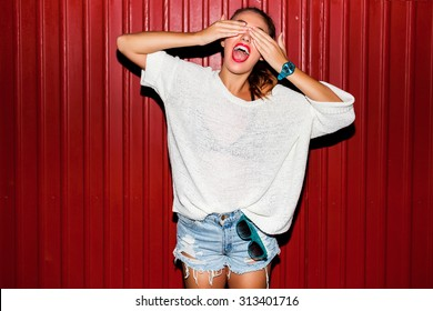 Young  pretty  hipster woman in trendy autumn clothes have fun and doing grimaces  near red  background  urban style  on  night party.  Bright flash ,  contrast color .