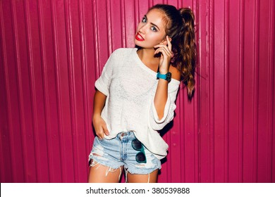 Young pretty hipster woman in trendy spring clothes have fun and doing grimaces near pink background urban style on night party. Bright flash , contrast color .