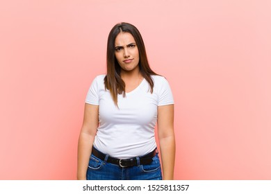 young pretty hispanic woman feeling confused and doubtful, wondering or trying to choose or make a decision against pink wall