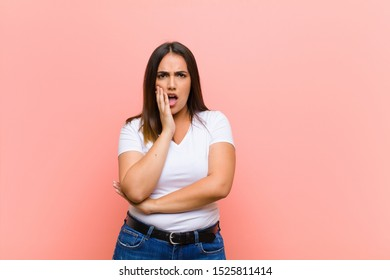 young pretty hispanic woman open-mouthed in shock and disbelief, with hand on cheek and arm crossed, feeling stupefied and amazed against pink wall