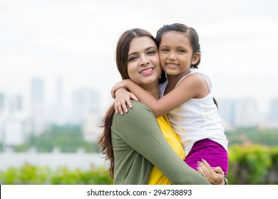Young pretty Indian woman carrying her little daughter