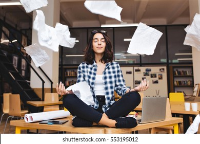 Young pretty joyful brunette woman meditating on table surround work stuff and flying papers. Cheerful mood, taking a break, working, studying, relaxation, true emotions