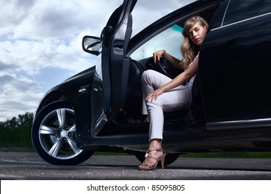 Young pretty lady with a modern luxury car