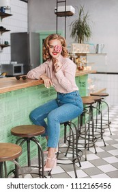 Young pretty lady in shirt and jeans sitting at the bar counter and covering her eye with lollipop candy while joyfully looking in camera in cafe