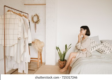 Young pretty lady with short black hair in glasses and linen beige robe sits on bed in morning in her big white room, smiles and looks on her wardrobe thinking what to wear today. Space for text.