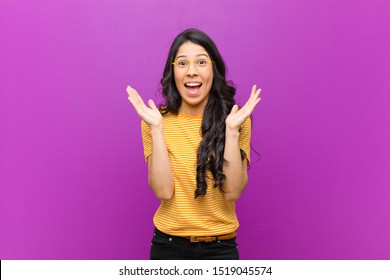 young pretty latin woman feeling shocked and excited, laughing, amazed and happy because of an unexpected surprise against purple wall