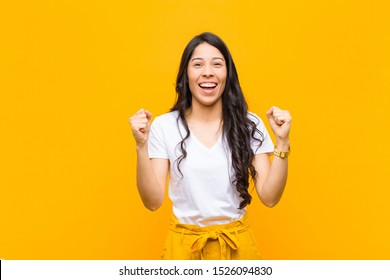 young pretty latin woman feeling happy, surprised and proud, shouting and celebrating success with a big smile against orange wall