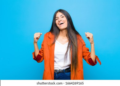 young pretty latin woman feeling happy, surprised and proud, shouting and celebrating success with a big smile against flat wall