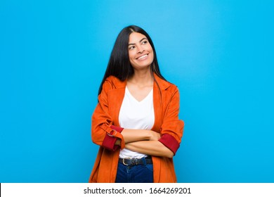 young pretty latin woman feeling happy, proud and hopeful, wondering or thinking, looking up to copy space with crossed arms against flat wall