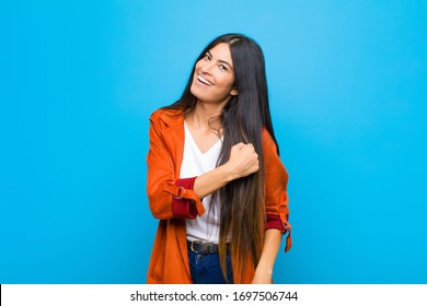 young pretty latin woman feeling happy, positive and successful, motivated when facing a challenge or celebrating good results against flat wall