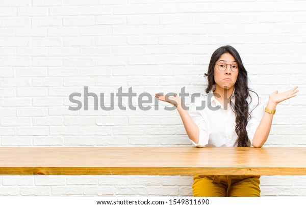 young  pretty latin woman feeling puzzled and confused, doubting, weighting or choosing different options with funny expression sitting in front of a table