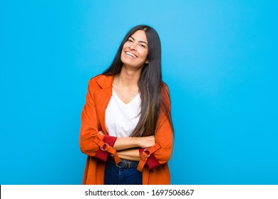 young pretty latin woman laughing happily with arms crossed, with a relaxed, positive and satisfied pose against flat wall