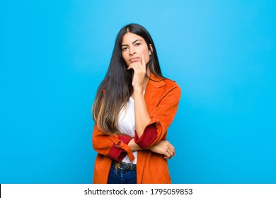 young pretty latin woman looking serious, thoughtful and distrustful, with one arm crossed and hand on chin, weighting options against flat wall