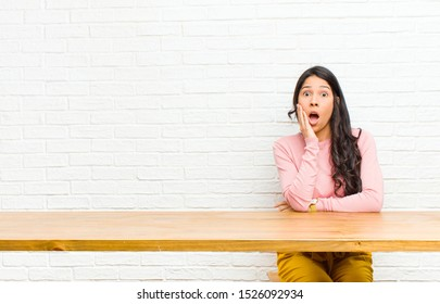young  pretty latin woman open-mouthed in shock and disbelief, with hand on cheek and arm crossed, feeling stupefied and amazed sitting in front of a table