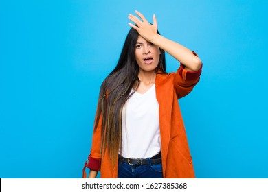 young pretty latin woman raising palm to forehead thinking oops, after making a stupid mistake or remembering, feeling dumb against flat wall