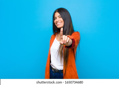 young pretty latin woman smiling proudly and confidently making number one pose triumphantly, feeling like a leader against flat wall