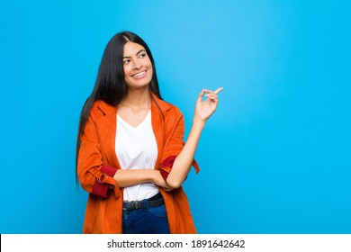 young pretty latin woman smiling happily and looking sideways, wondering, thinking or having an idea against flat wall