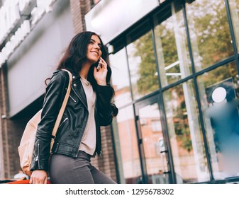 Young pretty latin woman walking near shops in city centre
