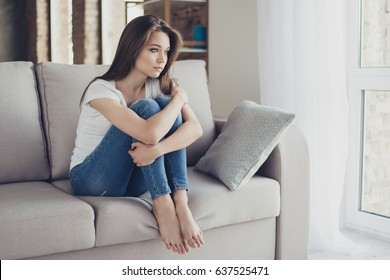 Young pretty lonely sad girl sitting on sofa and hugging her knees