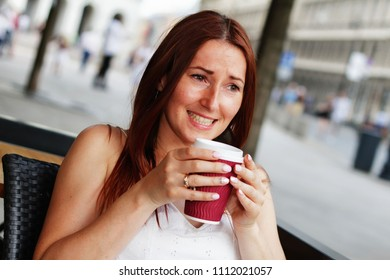 Young pretty long haired disgusted woman with golden ring on her finger sitting in the restaurant garden, holding mug of hot cofffee and showing her teeth