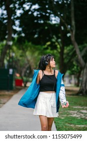 A young and pretty millennial teenager girl dances as she strolls through a park. The teenager is dressed sportily in a tank top, skirt and windbreaker.