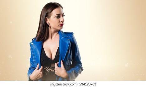 Young pretty model woman posing in studio with blue jacket on ocher background