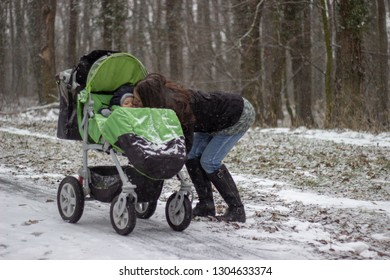 young pretty mother with brown hair is kissing her little adorable son sitting in the green stroller in snowy forest