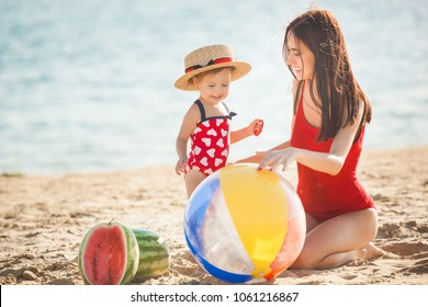 Young pretty mother playing with her little cute daughter at the beach. Loving mom having fun with her child at the sea shore