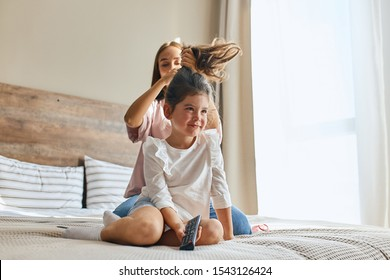 Young pretty mother prepares little charming daughter to kindergarten, holding long brunette hair, putting scrunchy, doing hairstyle while little kid watching funny cartoons, morning time concept