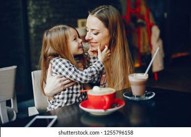 young and pretty mother sitting at the cafe with her little daughter