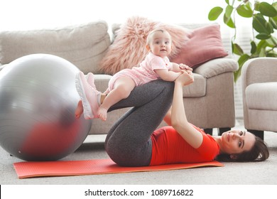 Young pretty mother working out with her little child at home