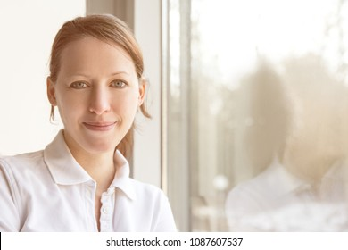 young pretty nurse in front of a window, with reflection and copyspace