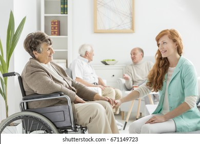 Young pretty nurse talking to old lady in wheelchair