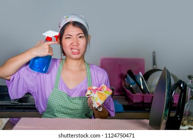 young pretty overworked and frustrated Asian Chinese service maid woman working domestic cleaning and washing home kitchen stressed and upset pointing spray bottle to head as a gun
