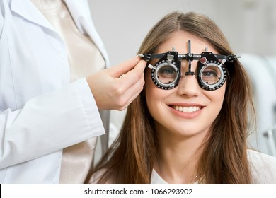 Young pretty patient wearing visual inspection device during admission to an ophthalmologist. Health saving, vision imroving. Feeling satisfied. Doctor is giving advices.