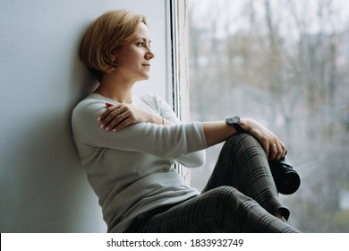 young pretty photographer girl sitting on window sill with camera in hand and thoughtfully looking outside