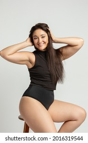 Young pretty plus size or plump woman celebrating her natural body. Positive beautiful female model in black underwear against white background. Lifestyle portrait with minimal makeup