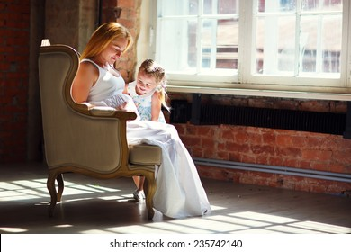 A young pretty pregnant woman with long blonde hair sitting in a chair opposite the window and hugging her little cute daughter. Happy family concept. Parents and kids relationship.