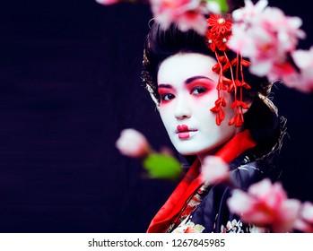 young pretty real geisha in kimono with sakura and decoration on